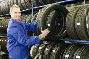 Mann im Reifenlager holt neue Autoreifen